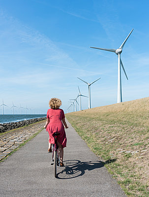 Girl cycling along windfarm - p1132m1591230 by Mischa Keijser