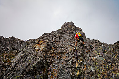 Low angle view of determined hiker climbing mountain against sky - p1166m1531492 by Cavan Images