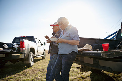 Senior farmer couple eating lunch, taking a break at pickup truck on sunny farm - p1192m2040218 by Hero Images