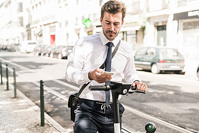 Young businessman with e-scooter using mobile phone in the city, Lisbon, Portugal - p300m2144884 by Uwe Umstätter