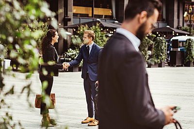 Male and female entrepreneurs shaking hands while standing outdoors - p426m2170283 by Maskot