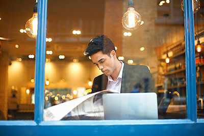 Window view of businessman reading broadsheet news in cafe - p429m1418083 by Peter Muller