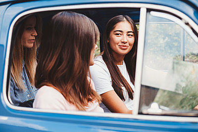 Friends talking inside car - p429m2097345 by Lorenzo Antonucci