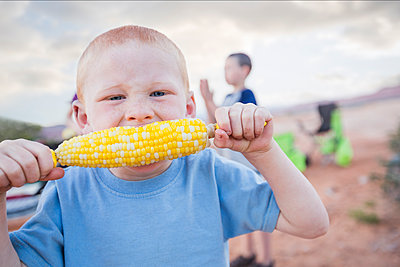 Caucasian boy eating corn on the cob - p555m1304836 by Mike Kemp