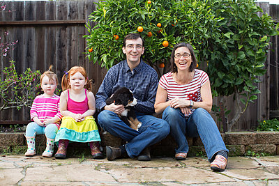 Portrait of young family with dog, sitting in garden - p924m1404281 by Paige Green Photography
