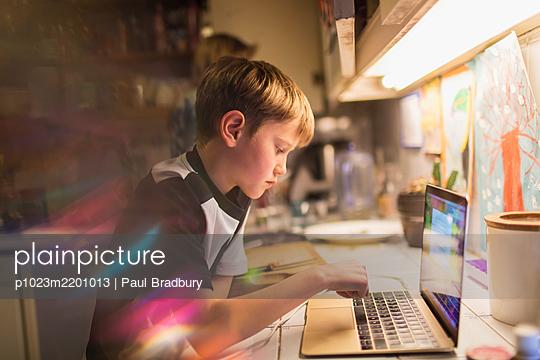 Focused boy doing homework at laptop in kitchen - p1023m2201013 by Paul Bradbury