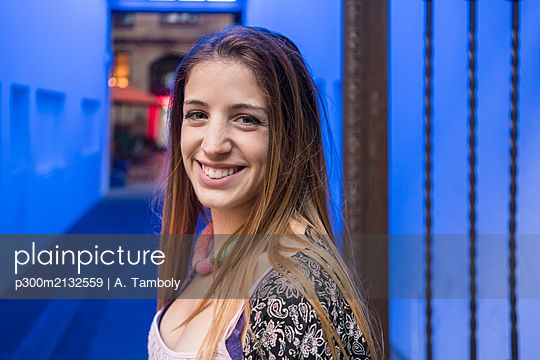 Portrait of smiling young woman with blue illuminated background - p300m2132559 by A. Tamboly