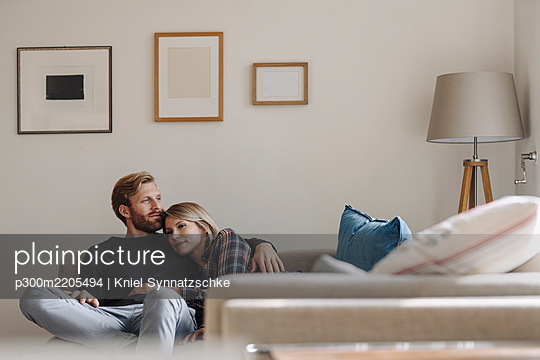 Relaxed couple on sofa at home - p300m2205494 by Kniel Synnatzschke