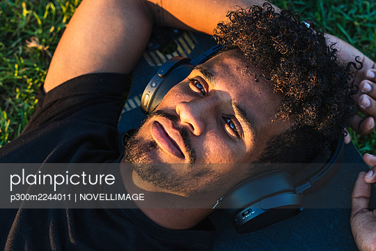 Close-up of thoughtful man listening music over headphones while lying on skateboard in park - p300m2244011 by NOVELLIMAGE