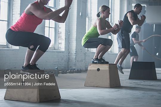 Athletes crouching on platforms in gym - p555m1411994 by John Fedele