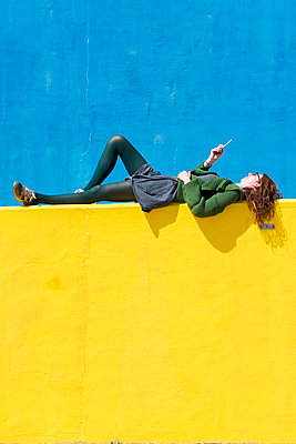Side view of businesswoman using smart phone while lying on yellow wall during sunny day - p1166m2060575 by Cavan Social