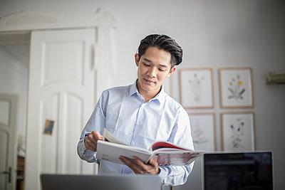Asiatischer Unternehmensgründer liest eine Fachzeitschrift - p1284m1541357 von Ritzmann
