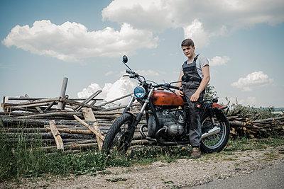 Junger Mann mit Motorrad am Straßenrand - p1437m1584897 von Achim Bunz