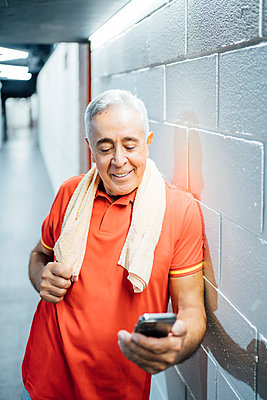 Smiling senior man having a break and using cell phone in gym - p300m2181046 by Oscar Carrascosa Martinez