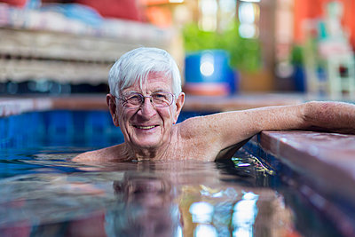Smiling Caucasian man in swimming pool - p555m1522931 by Marc Romanelli