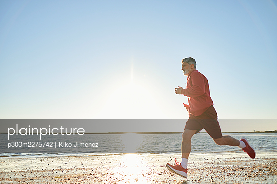 Male runner jogging at beach during sunset - p300m2275742 by Kiko Jimenez