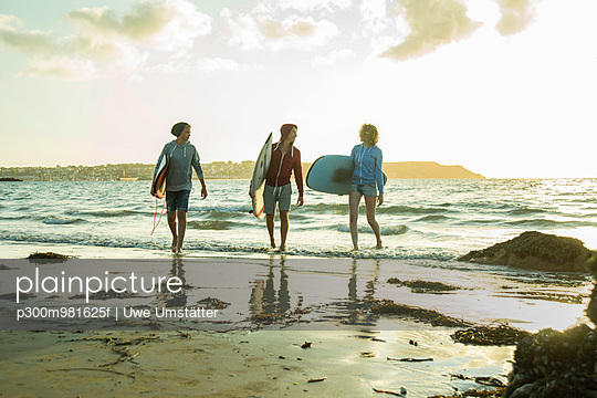 Three teenagers with surfboards walking on the beach at evening twilight - p300m981625f by Uwe Umstätter