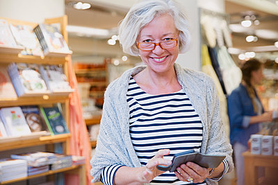 Portrait smiling mature female shopper using cell phone in shop - p1023m1443265 by Sam Edwards
