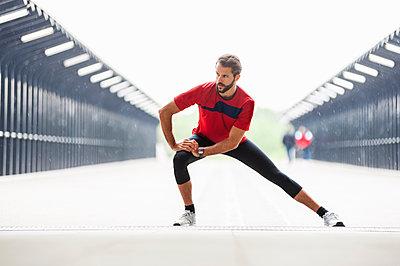 Man stetching on a bridge - p300m1587066 by Daniel Ingold