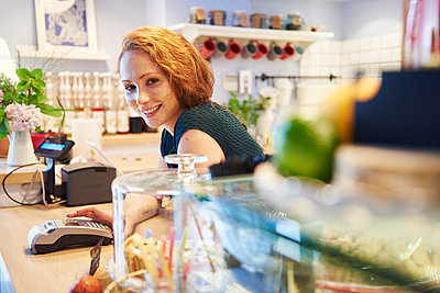 Portrait of smiling young woman with card reader at the counter in a cafe - p300m2023648 von gpointstudio