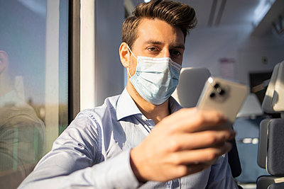 Mid adult businessman with face mask using smart phone while traveling by train during COVID-19 - p300m2242890 by Ignacio Ferrándiz Roig