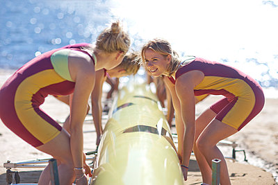 Female rowers lifting up boat - p300m975558f by zerocreatives