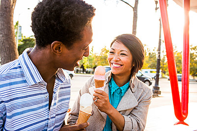 Smiling couple eating ice cream in park - p555m1411239 by Adam Hester