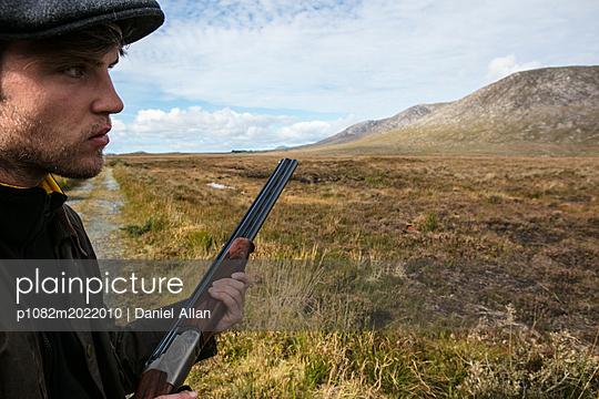 Mann mit Jagdgewehr im Profil - p1082m2022010 von Daniel Allan