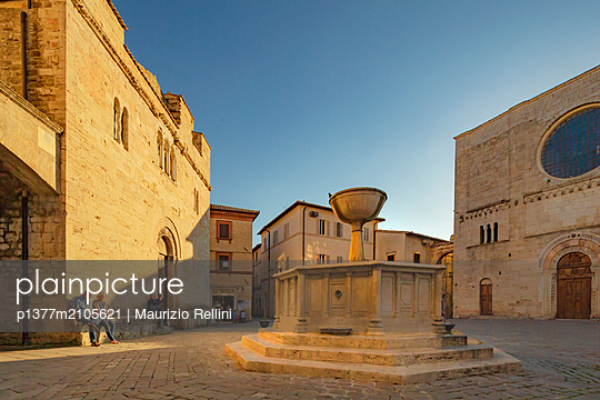 Italy, Umbria, Perugia district, Bevagna, People in Piazza Silvestri at sunset with the medieval fountain and the Cathedral in the background - p1377m2105621 by Maurizio Rellini