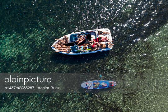 Junge Leute chillen auf einem Motorboot, Luftaufnahme - p1437m2283287 von Achim Bunz