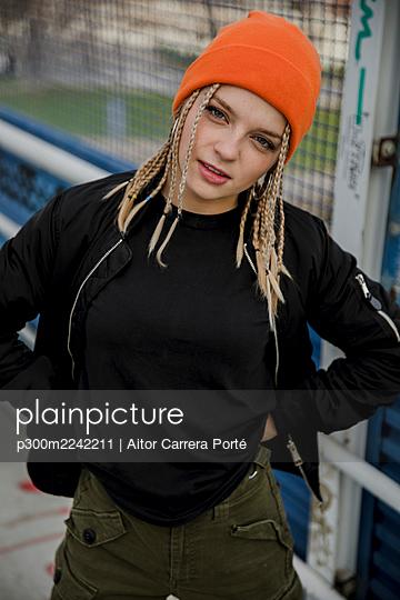 Portrait of beautiful woman wearing orange knit hat standing on bridge - p300m2242211 by Aitor Carrera Porté