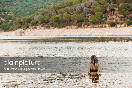 Young woman bathing in lake - p300m2256351 by Manu Reyes