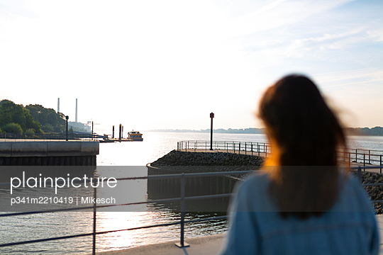 Young woman looks out over the Elbe river - p341m2210419 by Mikesch