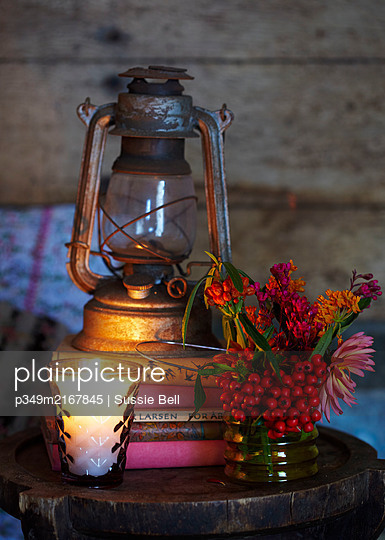 Lit candle and cut flowers with hurricane lamp on books in Autumn  UK - p349m2167845 by Sussie Bell