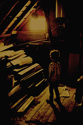 Young boy looking at strange light in attic - p1028m2007748 by Jean Marmeisse