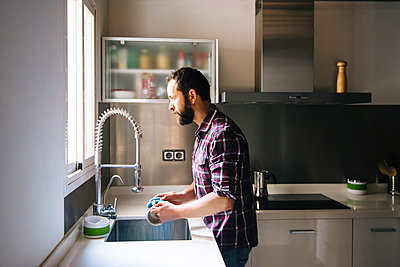 Man with beard and plaid shirt washing dishes at home. - p1166m2095948 by Cavan Images