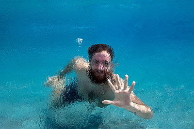 Man swims in glass pool on vacation - p1166m2096069 by Cavan Images