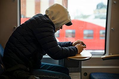 Teenage boy uses mobile phone on local train - p1687m2277795 by Katja Kircher