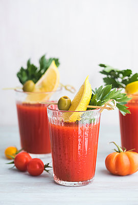 Glasses of fresh spicy tomato juice with cellery garnished with lemon slice, green olive and parsley - p300m2029333 by Ina Peters