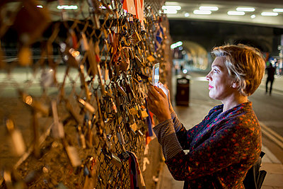 Mature woman photographing love locks with digital tablet at night, London, UK - p429m999644 by dotdotred