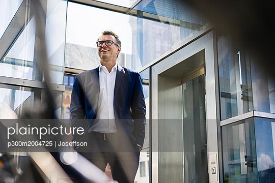 Smiling mature businessman standing outdoors - p300m2004725 von Joseffson