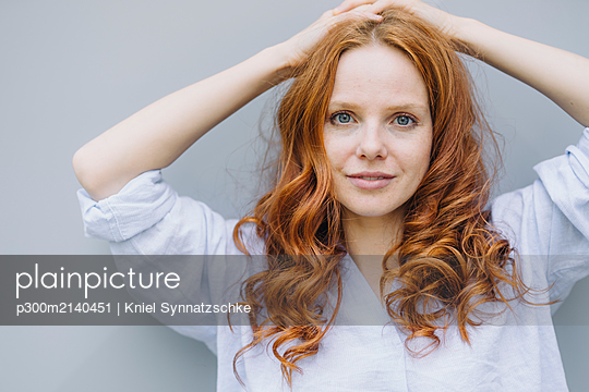 Portrait of beautiful redheaded woman at a wall - p300m2140451 by Kniel Synnatzschke