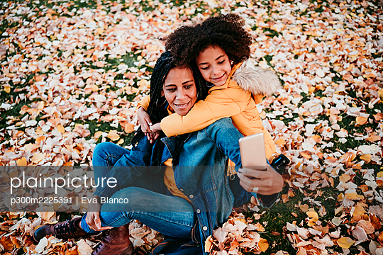 Girl embracing mother taking selfie through smart phone while sitting on autumn leaves - p300m2225391 by Eva Blanco