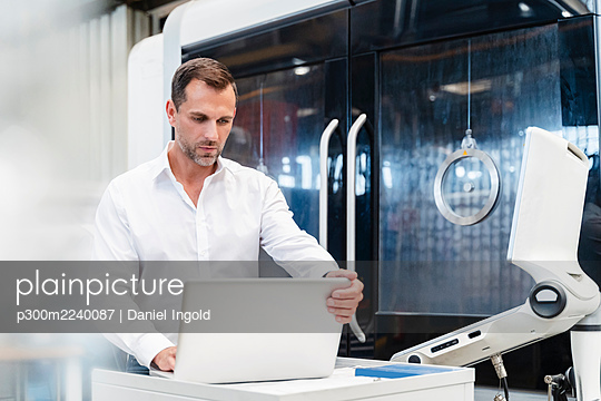 Male entrepreneur working on laptop while standing in factory - p300m2240087 von Daniel Ingold