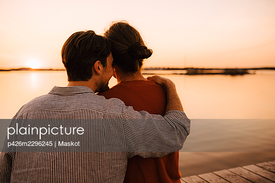 Rear view of gay couple spending leisure time at lakeshore - p426m2296245 by Maskot