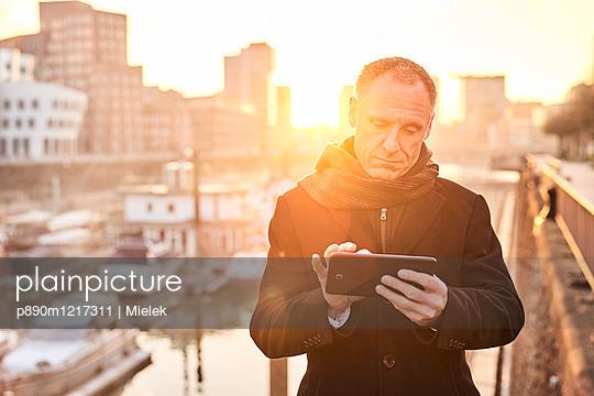 Man using tablet in Media harbour Düsseldorf - p890m1217311 by Mielek