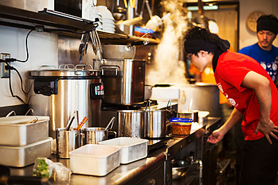 The ramen noodle shop.  Staff preparing food in a tiny kitchen  - p1100m1185677 by Mint Images