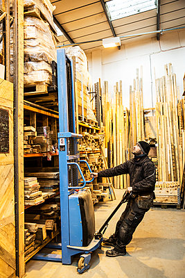 Man standing in warehouse using forklift to move pallet of wood off a shelf. - p1100m1575738 by Mint Images