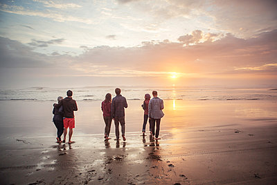 Rear view of couples walking on shore at beach during sunset - p1166m1534019 by Cavan Images