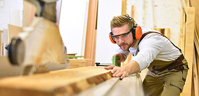 Carpenter using sawing machine in his workshop - p300m1192227 by lyzs